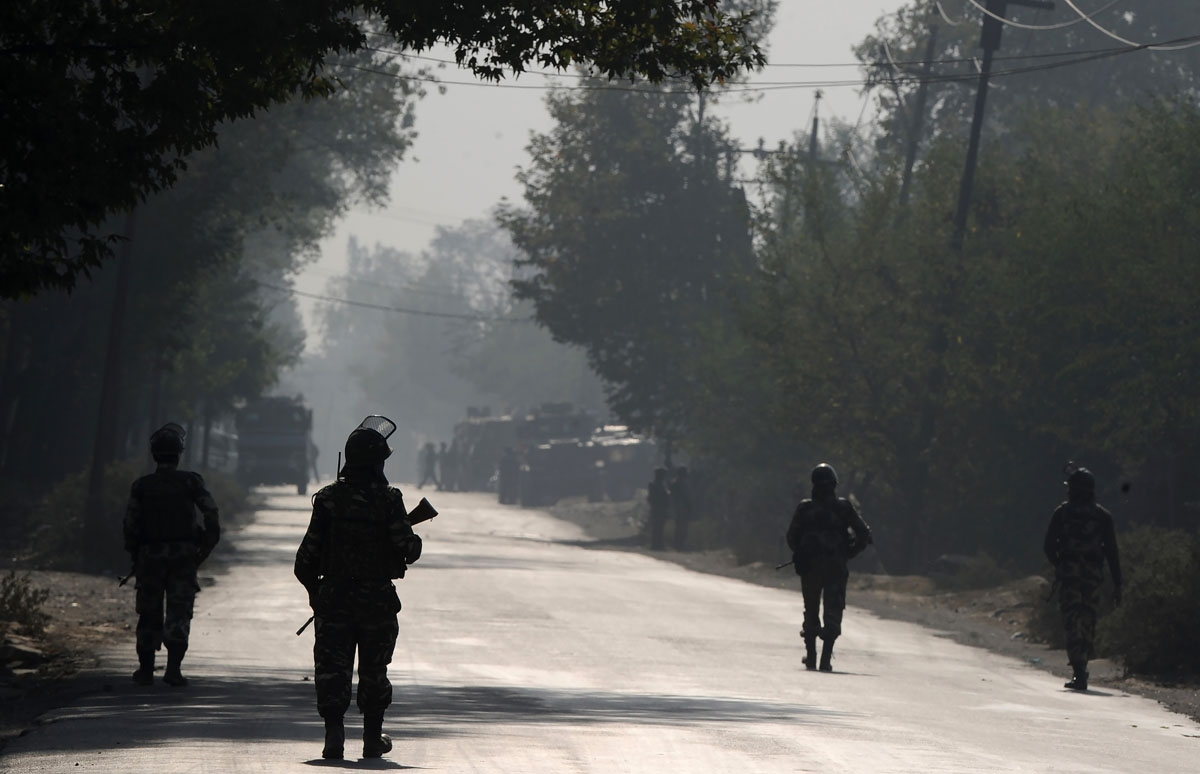 Indian paramilitary troopers patrol on the third day, near the site of a gunfight between the Indian army and suspected militants in Pampore, south of Srinagar on October 12, 2016