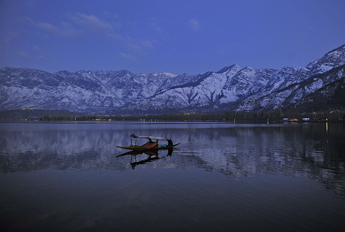 A boat passes in front of snow-covered mountains, on the Dal Lake, in Srinagar on January 1, 2011.
