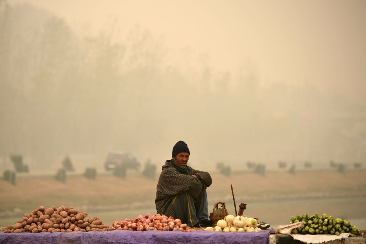 A vegetable vendor waits for customers on the banks of Dal lake in Srinagar on November 22,2016.