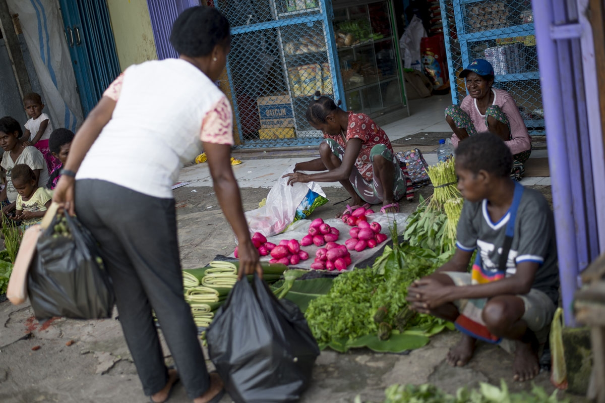 A Papuan woman shops for vegetables at street market in Timika in Indonesia's easternmost Papua province, on January 25, 2018.