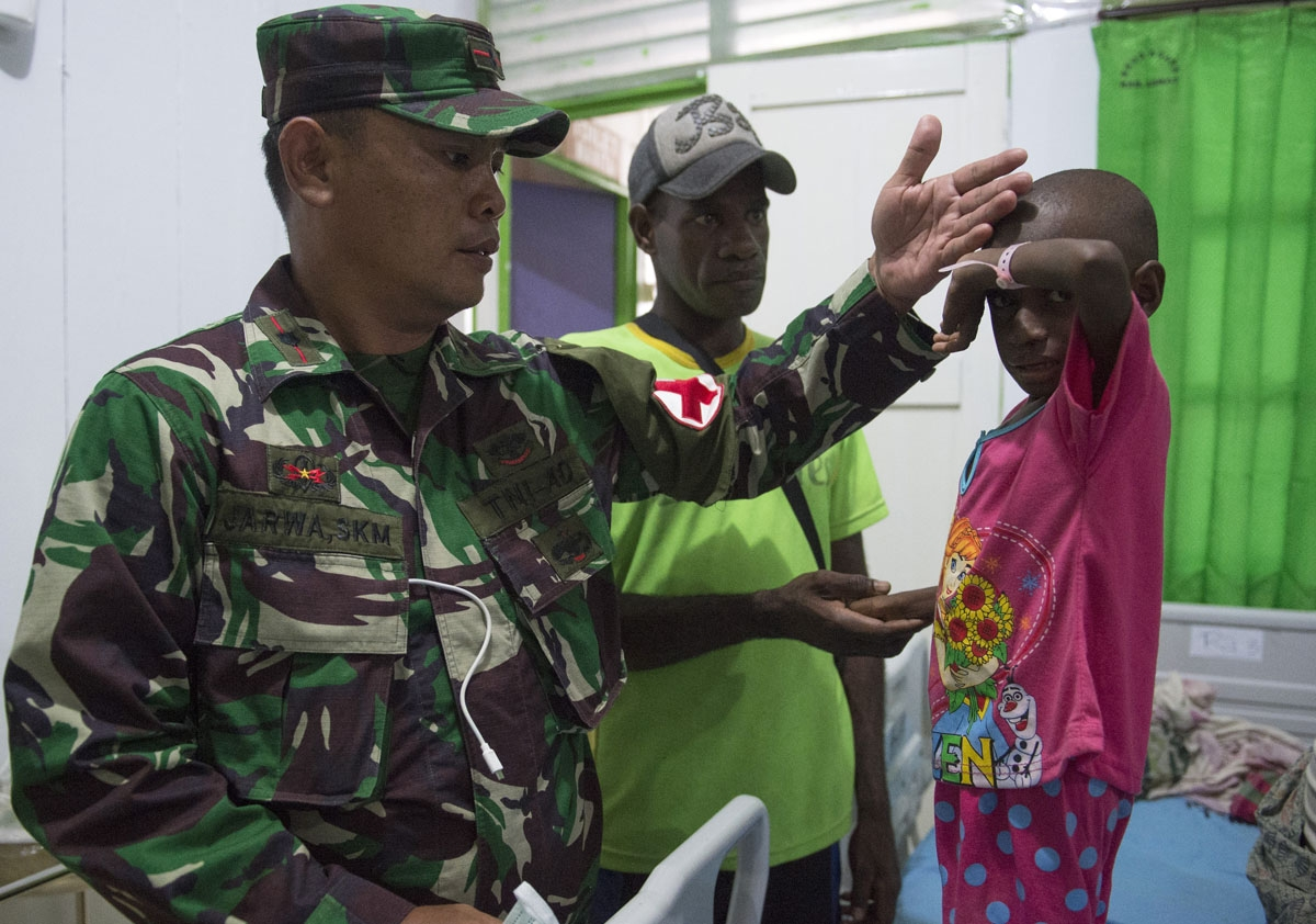 A member of an Indonesian military task force checks a child at a local hospital in Agats, the capital of Asmat district in Indonesia's easternmost Papua province, on January 26, 2018.