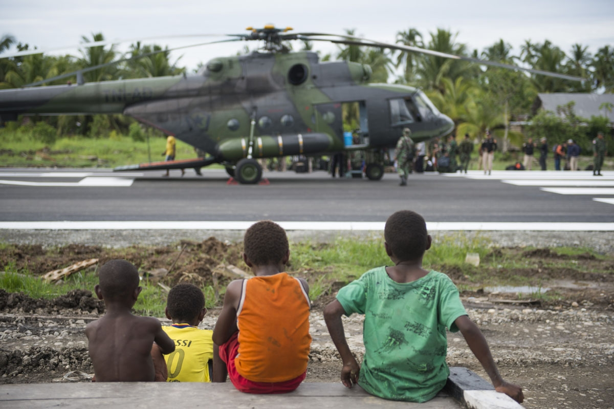 Three Papuan boys watch an Indonesian military Mi17 helicopter at Erwer airport in Agats, Asmat district, in West Papua on January 27, 2018.