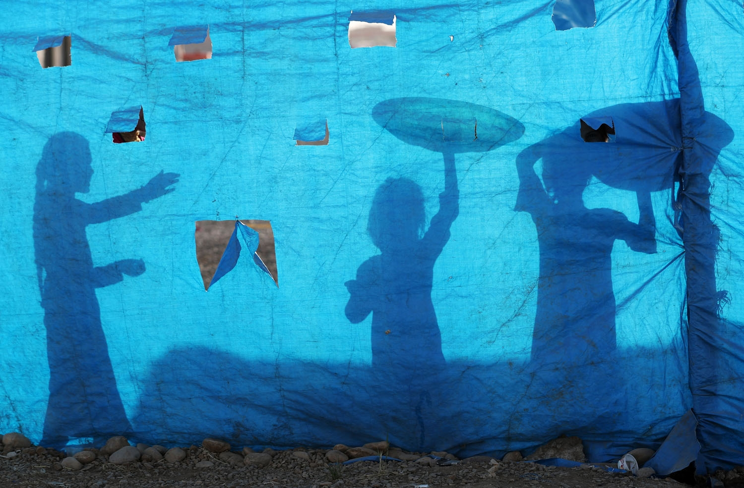 The silhouettes of Iraqi children are seen on tarpaulin as they collect water from a tank at the Al-Khazir camp for internally displaced people, located between Arbil and Mosul, on June 6, 2017.