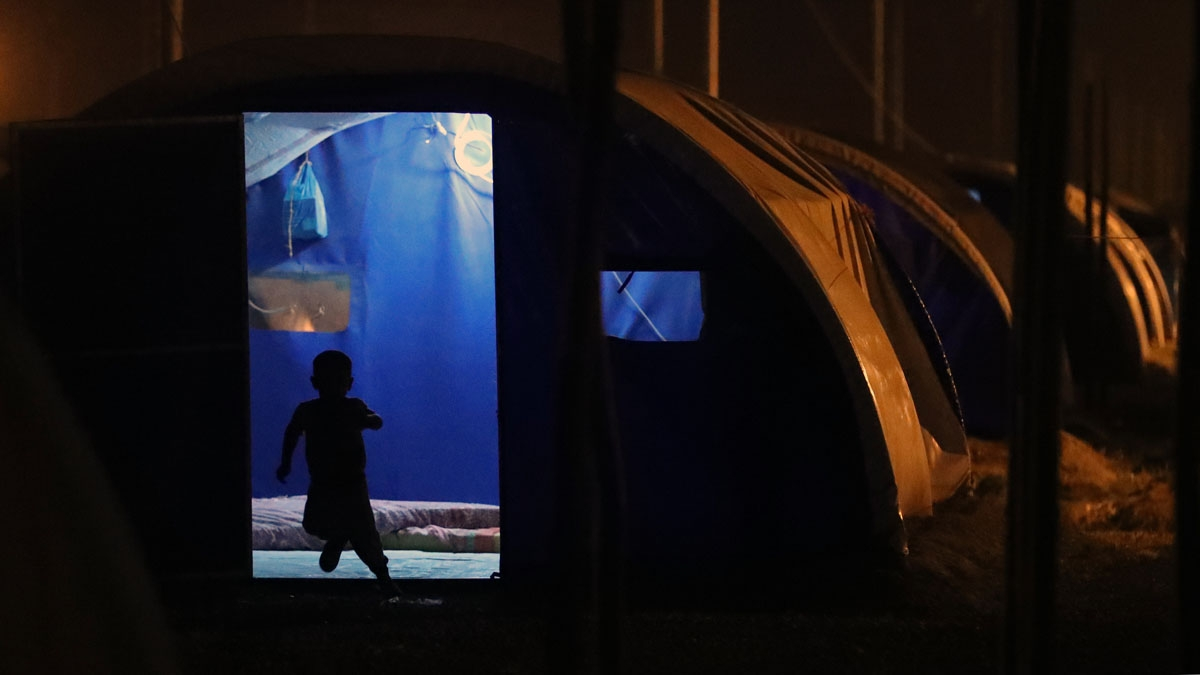 A child runs outside a tent after sunset on the first fasting day of the Muslim holy month of Ramadan, at al-Khazir camp for the internally displaced, located between Arbil and Mosul, on May 27, 2017