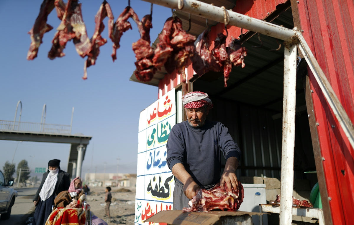 A butcher cuts a sheep into pieces as displaced Iraqi families, who fled their home, wait to be transferred to a camp, on November 28, 2016 in the village of Gogjali,