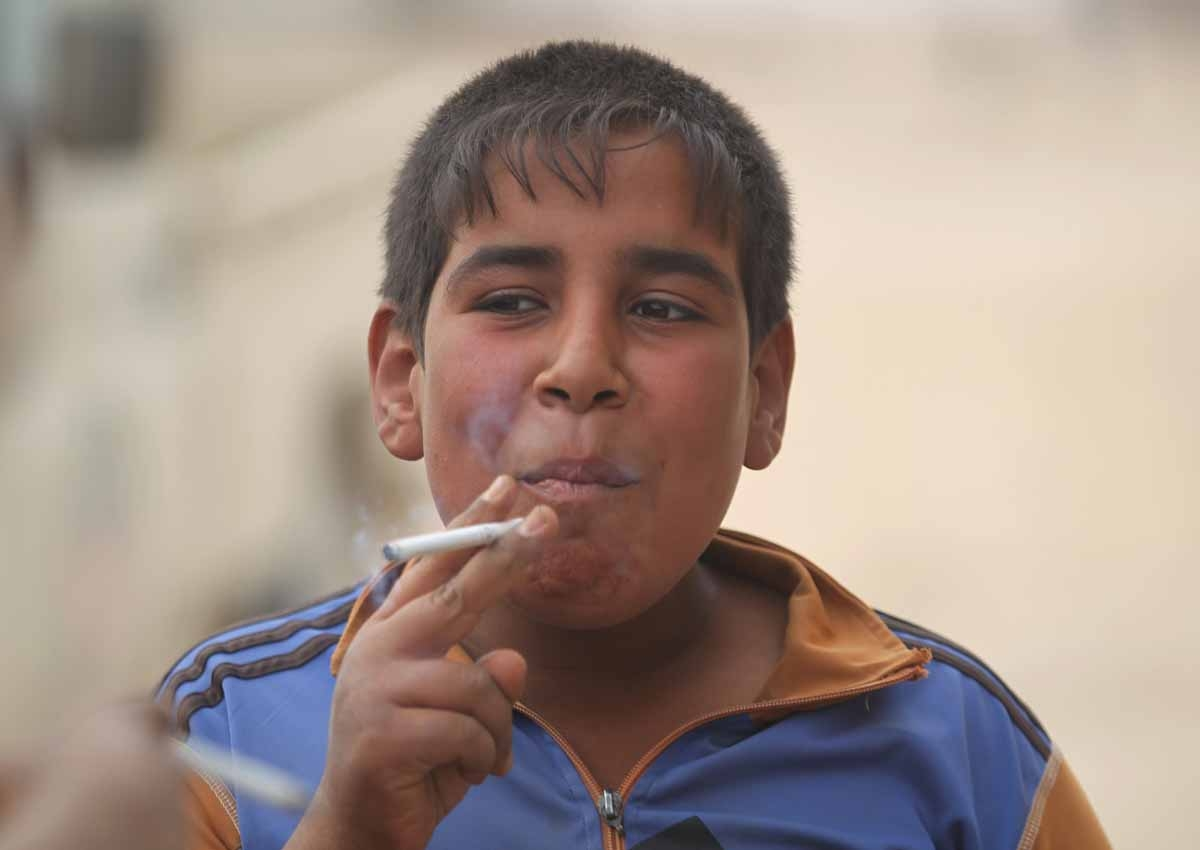 An Iraqi child smokes a cigarette upon the arrival of Iraqi forces in the village of Umm Mahahir, south of Mosul, on October 28, 2016 after troops recaptured it from the Islamic State (IS) group jihadists as part of their operation to retake the main hub