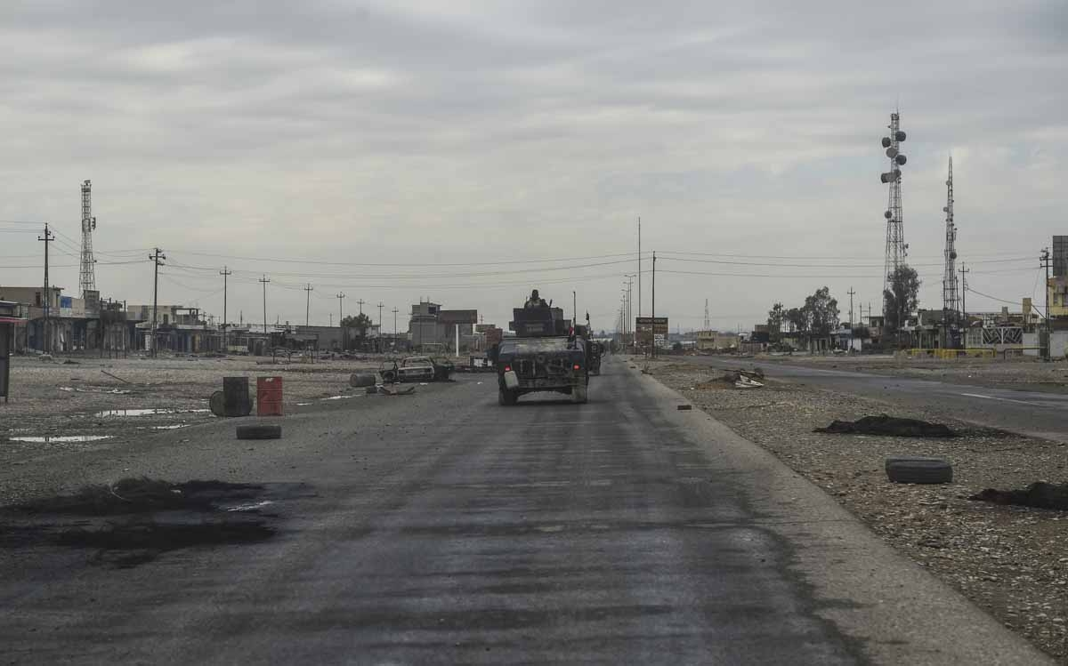 Iraqi army vehicles drive through the village of Gogjali, a few hundred metres of Mosul's eastern edge, on November 2, 2016, as they head towards the city during the ongoing operation to retake it from Islamic State group jihadists.