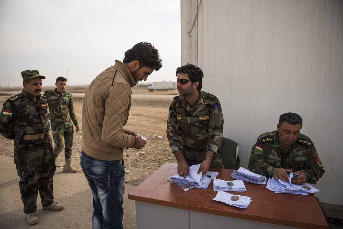 A man tries to convince Peshmerga forces to let him pass through the Iraqi Kurdish Shaqouli checkpoint, some 35 kilometres east of Mosul, on November 10, 2016.