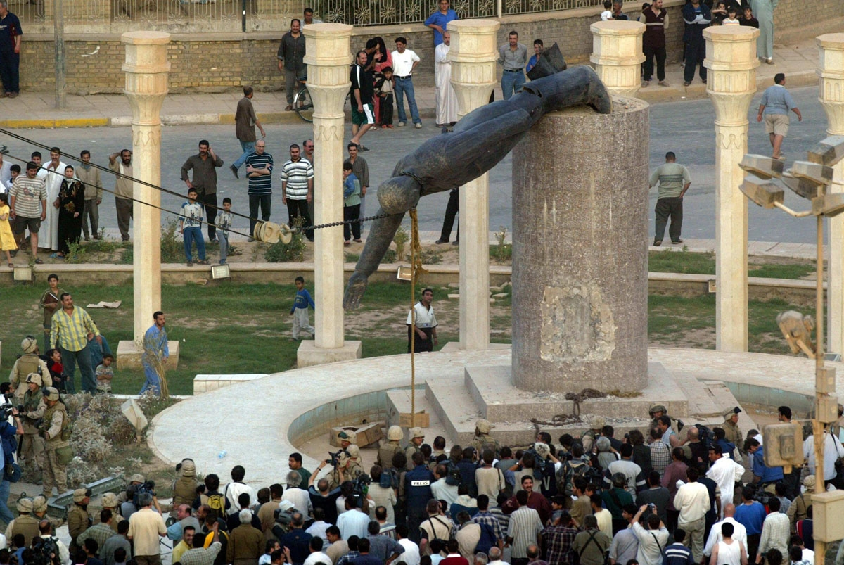 (FILES) In this file photo taken on April 9, 2003 Iraqis watch a statue of Iraqi President Saddam Hussein falling in Baghdad's al-Fardous (paradise) square.