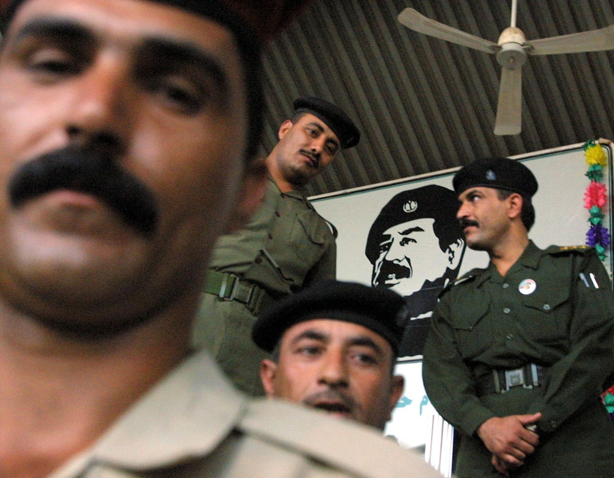 Iraqi officers stand under a huge portrait of President Saddam Hussein at Baghdad's National Stadium during a show in his support 14 October 2002. French Prime Minister Jean-Pierre Raffarin reiterated today that a military strike against Iraq must be a la