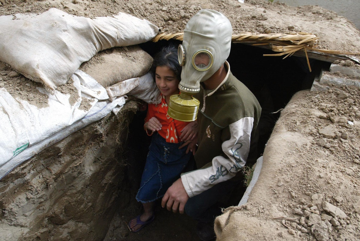 Iraqi Mustafa Mohammad, 13, wearing a WW II gas mask, plays with his sister Haya in a trench shored up by sandbags and bricks at their home garden in a Baghdad residential suburb 06 March 2003. Saddam made recently an appeal to his people to dig trenches
