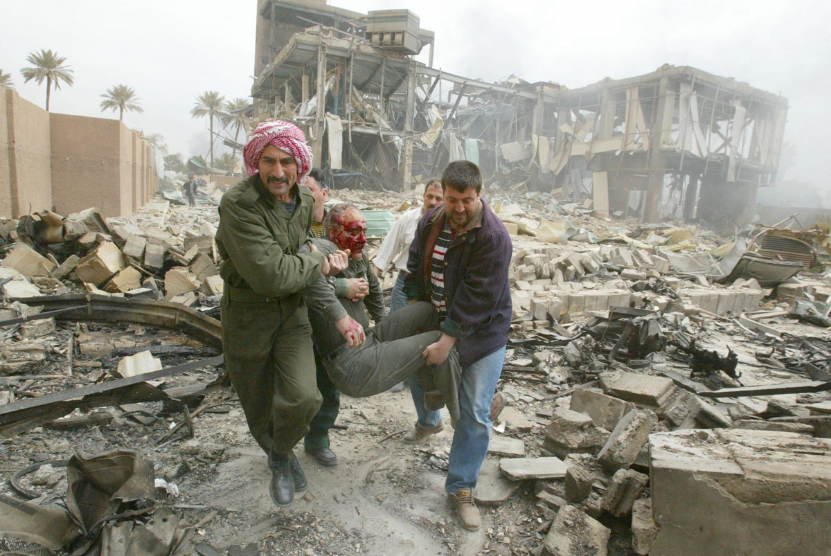 Iraqis carry an injured employee at the al-Salhiya telecomunications center after it was hit by a missile during a coalition air raid on Baghdad 30 March 2003. The raid took place as journalists were on a tour organized by the information ministry to be s
