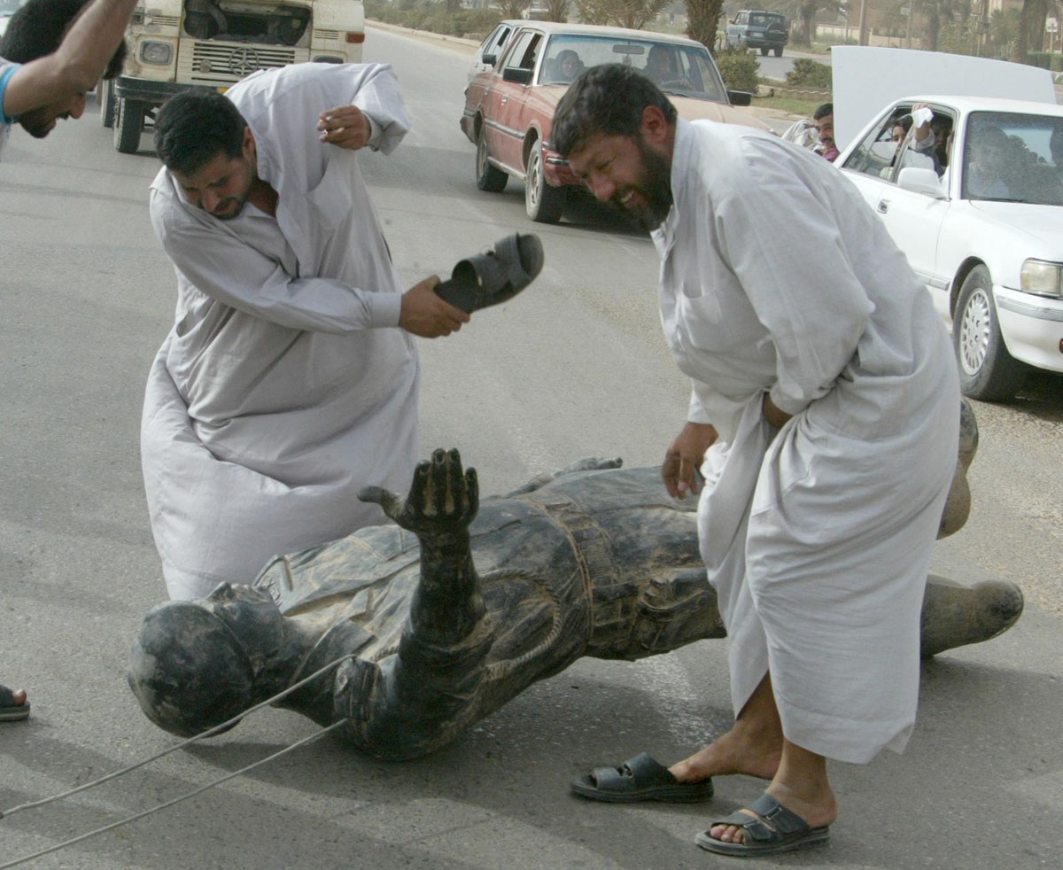 Iraqis hit a statue of Saddam Hussein with their sandals in Baghdad 09 April 2003 after it was pulled down as US tanks rolled into the heart of the Iraqi capital