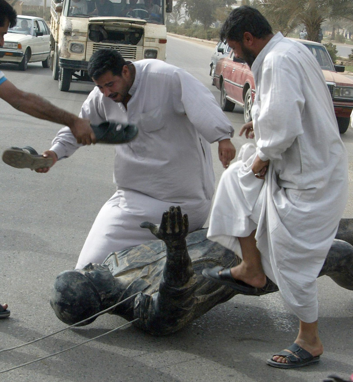 Iraqis hit and trample a statue of President Saddam Hussein in Baghdad 09 April 2003 after US tanks rolled into the heart of the Iraqi capital.