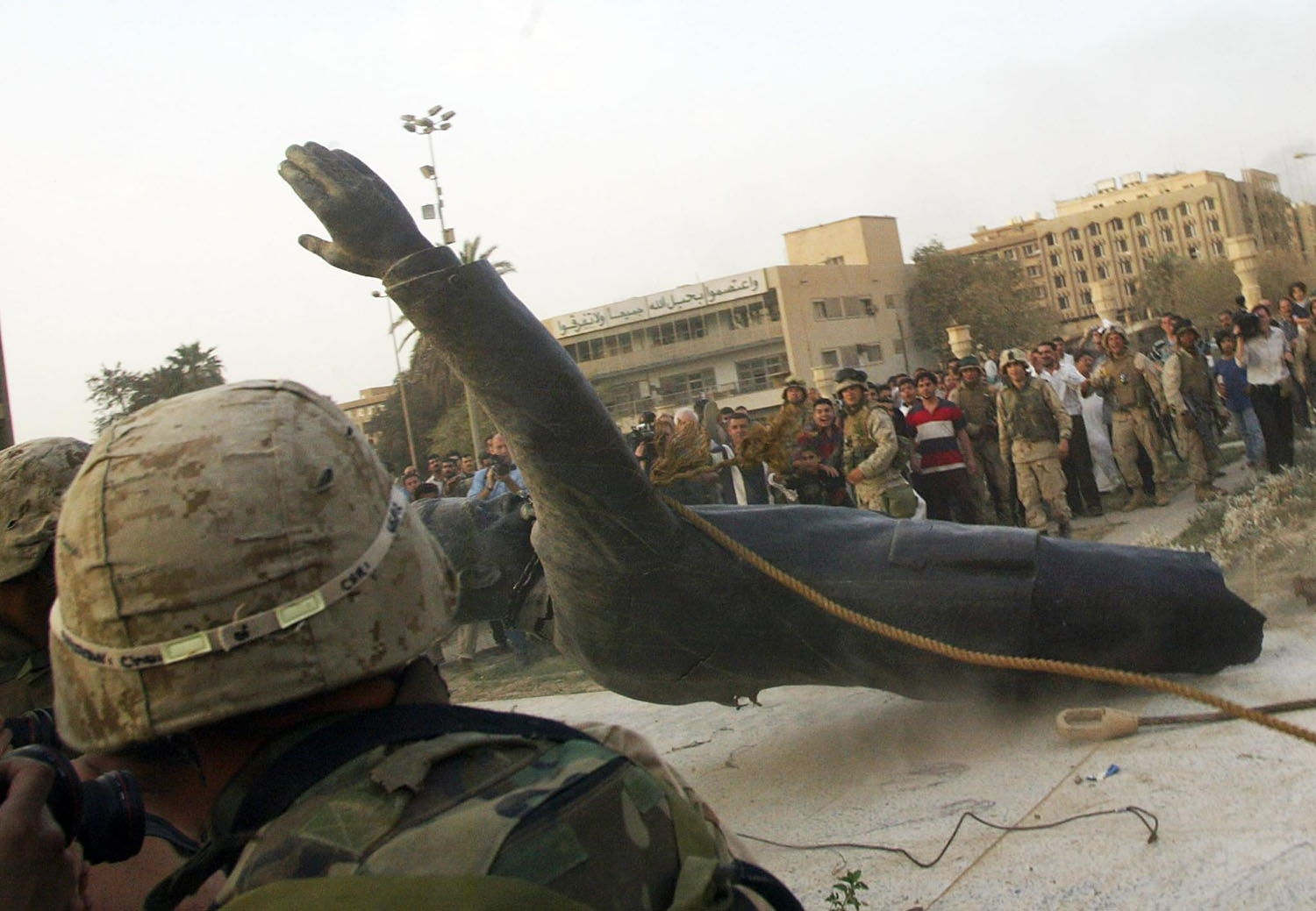 (FILES) In this file photo taken on April 9, 2003, a statue of Saddam Hussein falls as it is pulled down by a US armoured vehicle in Baghdad's al-Fardous square.
