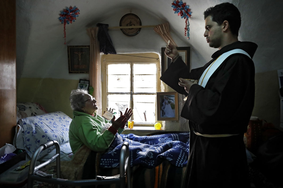 Franciscan friar Ayman Bathesh (R) gives communion to an elderly ill Christian woman at her home in the Old City of Jerusalem, on February 12, 2018.