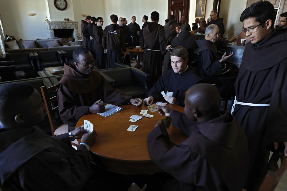 Franciscan friars play cards during a coffee break after lunch at the Saint Saviour Convent, the Franciscan headquarters in the Middle East, in the Old City of Jerusalem, on March 16, 2018.