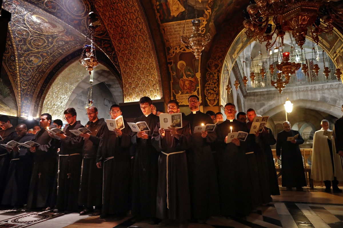 Franciscan friars pray and sing during the Lenten procession inside the Church of the Holy Sepulchre in the Old City of Jerusalem, on February 17, 2018.