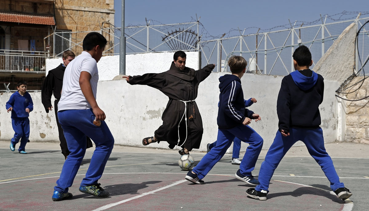 A Franciscan friar plays football with Palestinian children from the Terra Sancta school during a sport session in the Old City of Jerusalem, on March 1, 2018.