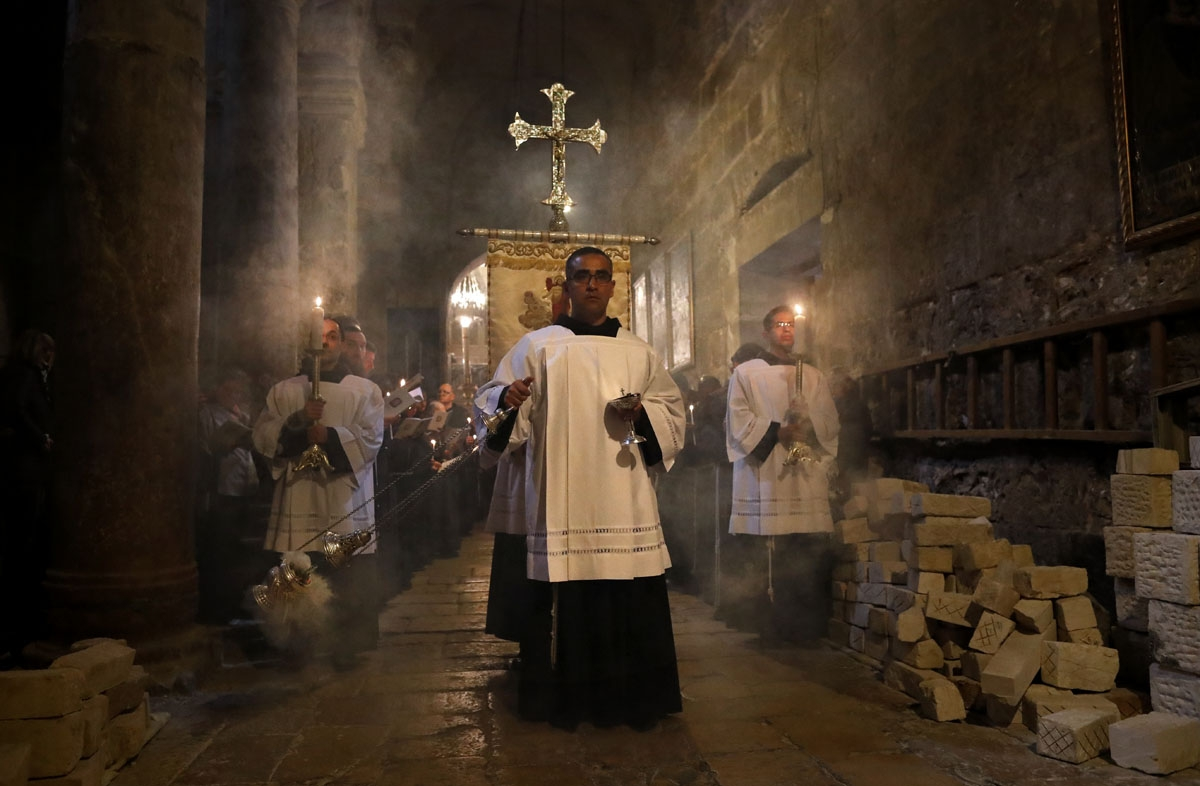 Franciscan friars pray during the Lenten procession inside the Church of the Holy Sepulchre in the Old City of Jerusalem, on February 17, 2018.
