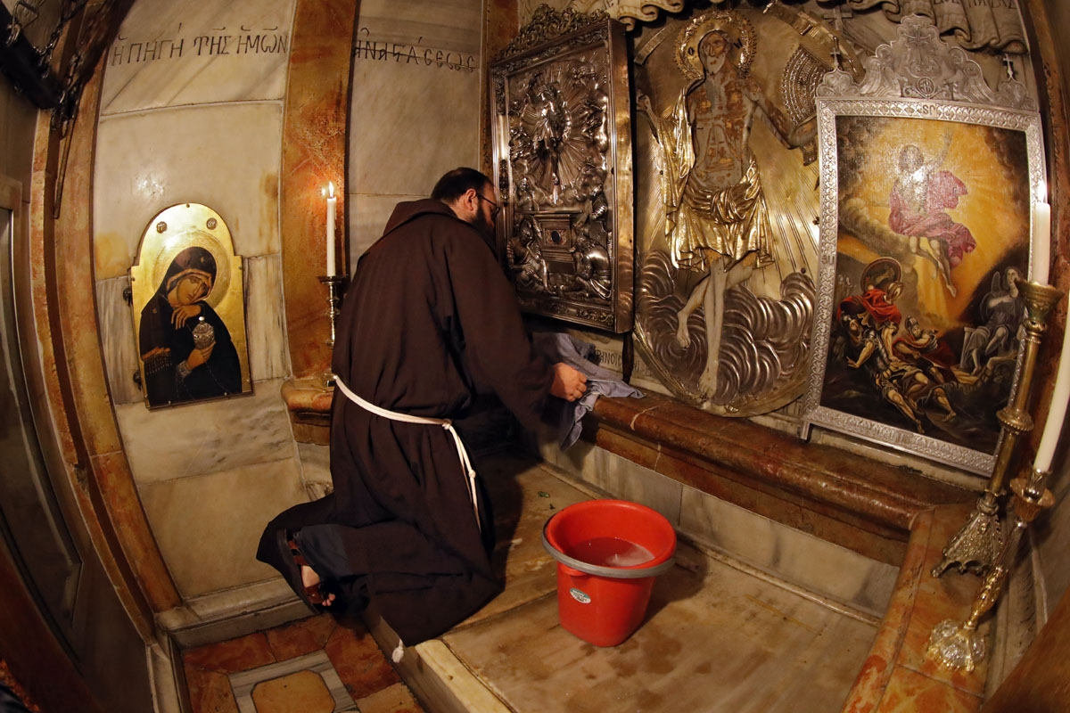 Croatian friar Sinisa Srebrerovic cleans the ornaments inside a tomb believed to the burial site of Jesus Christ on March 2, 2018.    Dispatched to the city 800 years ago by the Catholic order's founder, Saint Francis of Assisi, the Franciscans have for c