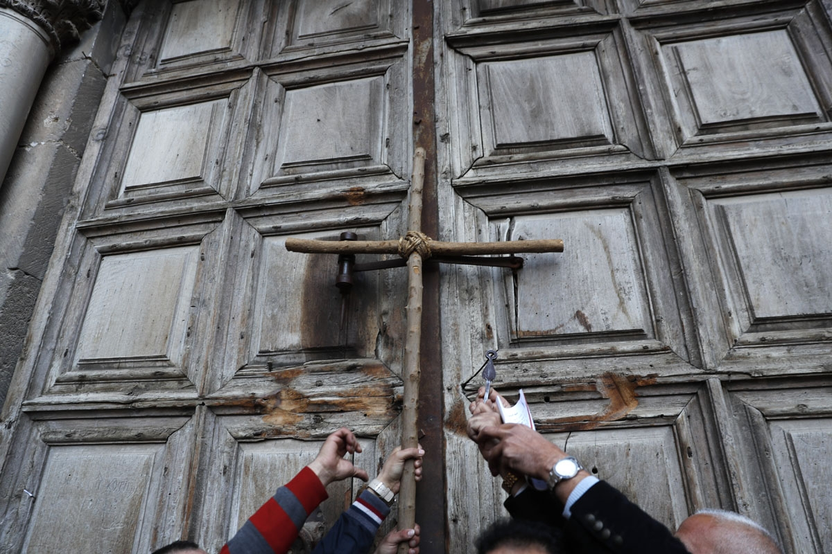 Protestors hold a cross during a demonstration outside the closed gate of the Church of the Holy Sepulchre in Jerusalem's Old City on February 27, 2018.