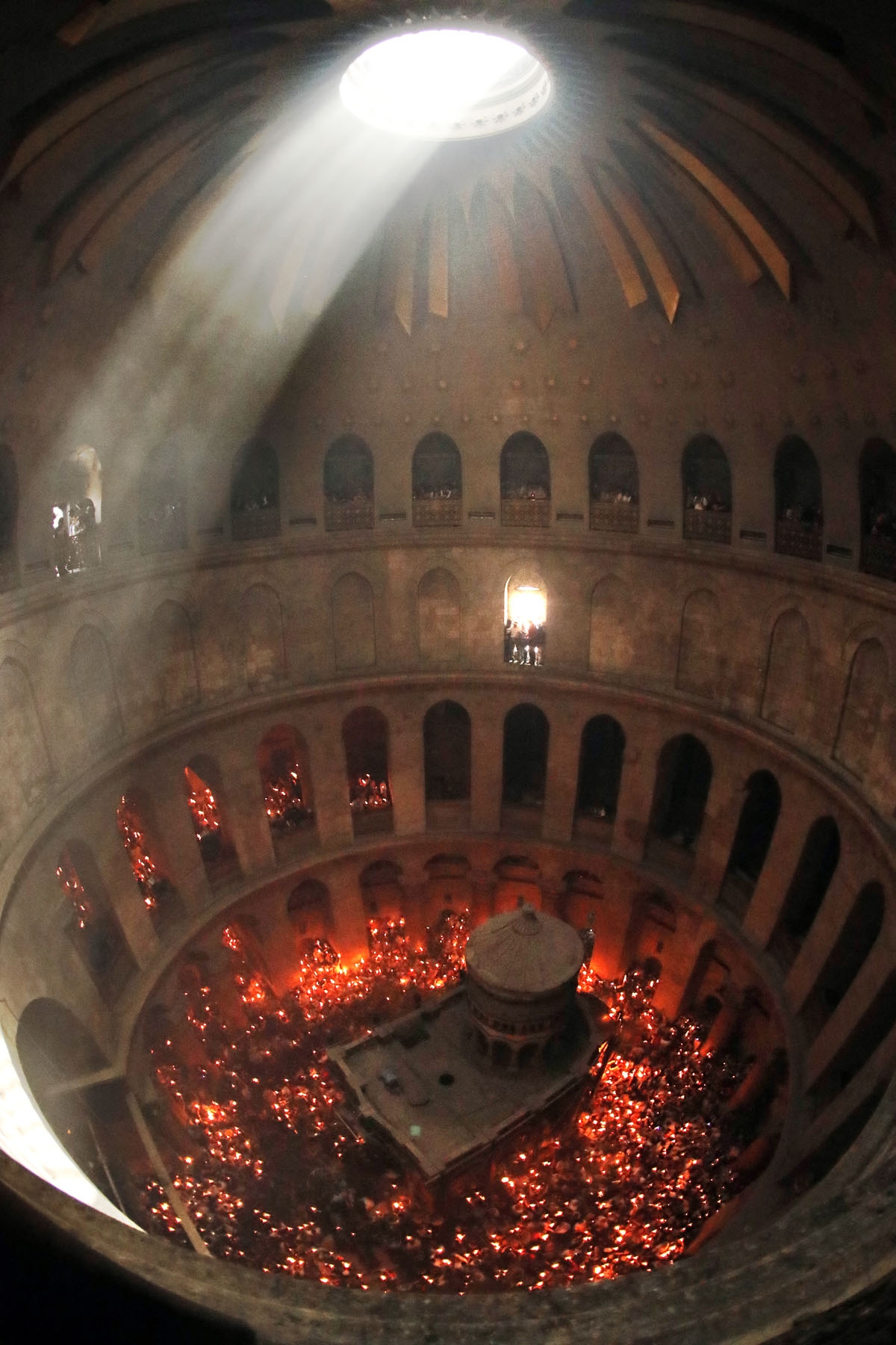 Christian Orthodox worshippers hold up candles lit from the Holy Fire as thousands gather in the Church of the Holy Sepulchre in Jerusalem's Old City, on April 30, 2016, during the Orthodox Easter ceremonies.