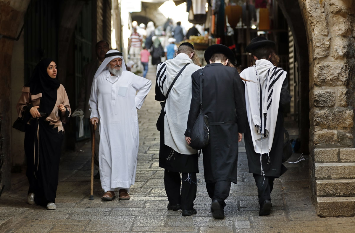 An elderly Palestinian man walks past a group of ultra Orthodox Jews in a street of Jerusalem's Old City on September 22, 2016.