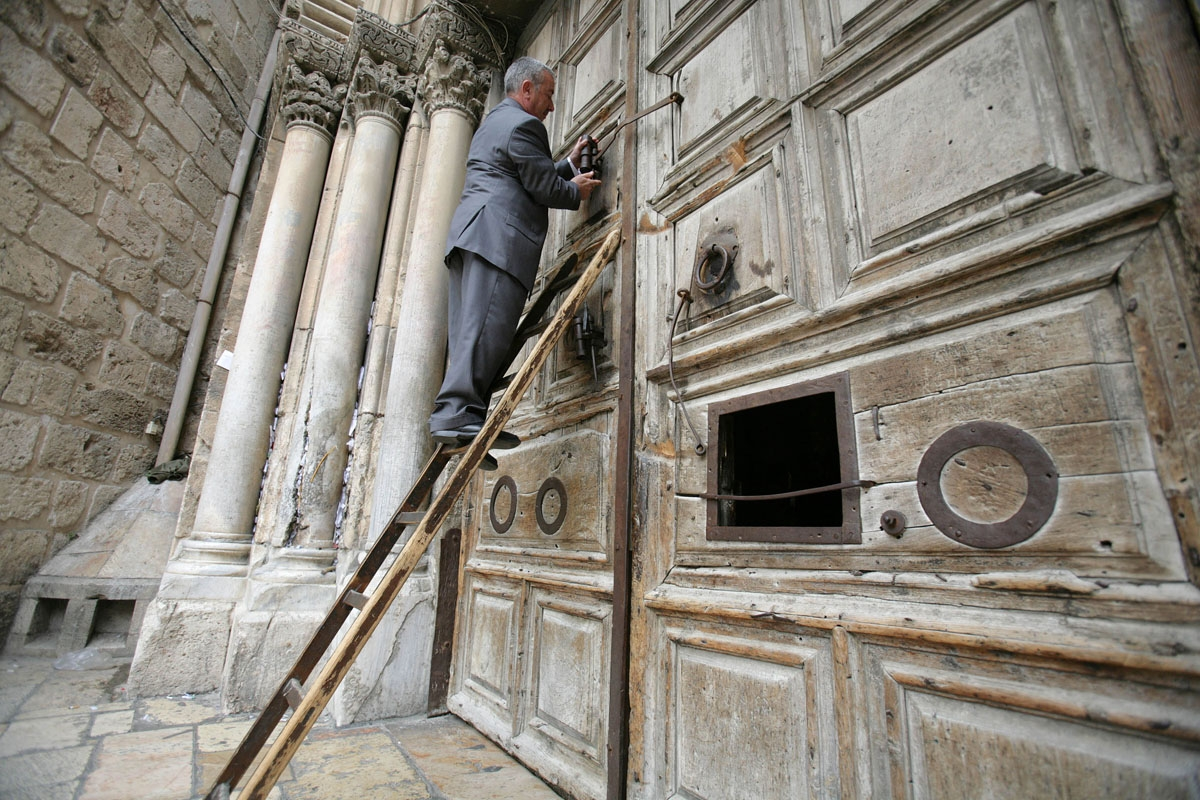 Wajih Nuseibeh, the latest member of an ancient Muslim family charged with opening and closing the doors of the Church of the Holy Sepulchre, climbs on a ladder to open the door of the church, April 7, 2007.