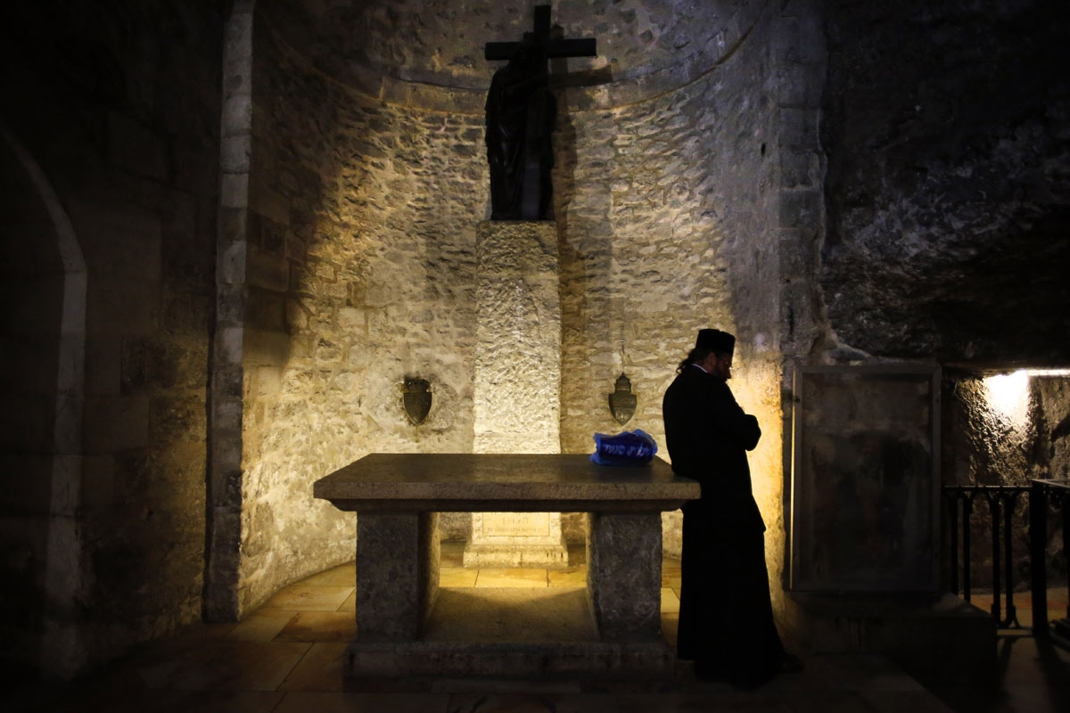 An Armenian priest prays inside the Armenian Chapel of Saint Helena in The Church of the Holy Sepulchre, also known as the Basilica of the Resurrection, one of Christianity's holiest sites in Jerusalem's old city on April 7, 2014.