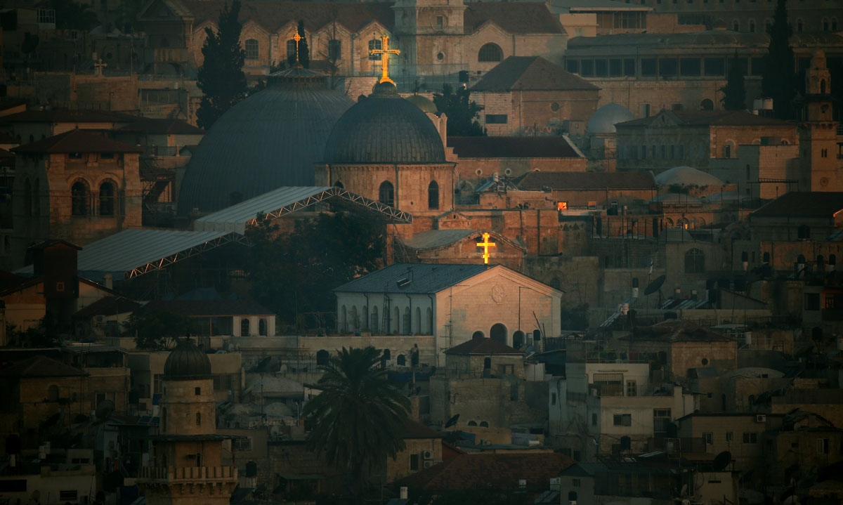A picture taken on July 28, 2014 shows the Holy Sepulchre church with its Christian cross shining at sunrise in the old city of Jerusalem. T