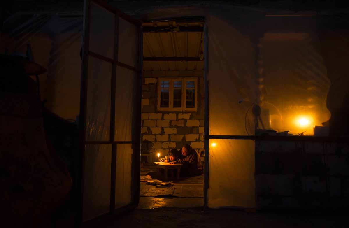 A Palestinian woman helps her son study by candlelight because of electricity shortages at their makeshift home in the Khan Yunis refugee camp in the southern Gaza Strip, April, 2017.