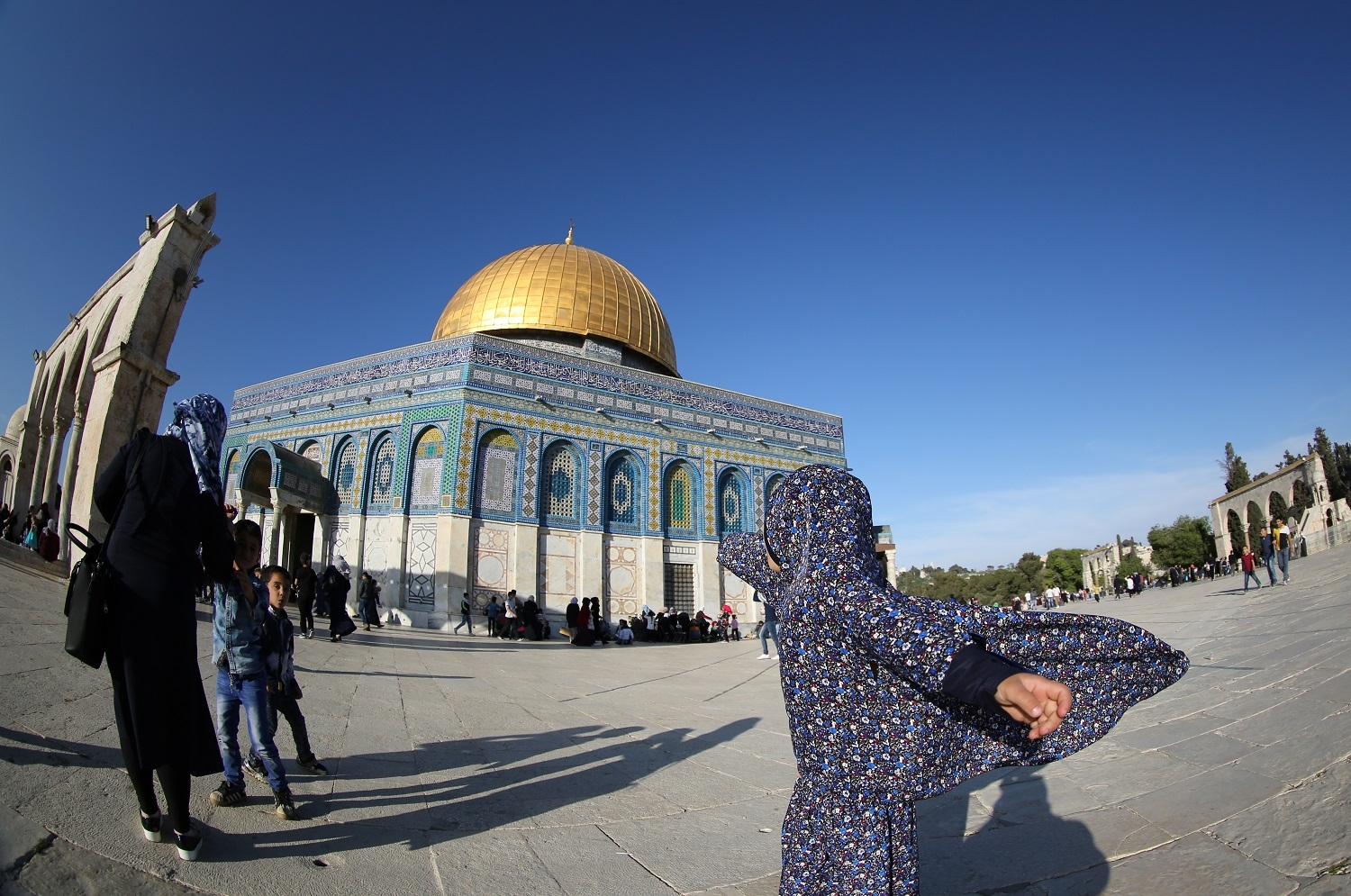 Palestinians walk in front of the Dome of the Rock mosque at the al-Aqsa mosque compound in Jerusalem's Old City on April 24, 2017.  / AFP PHOTO / Mahmud Hams