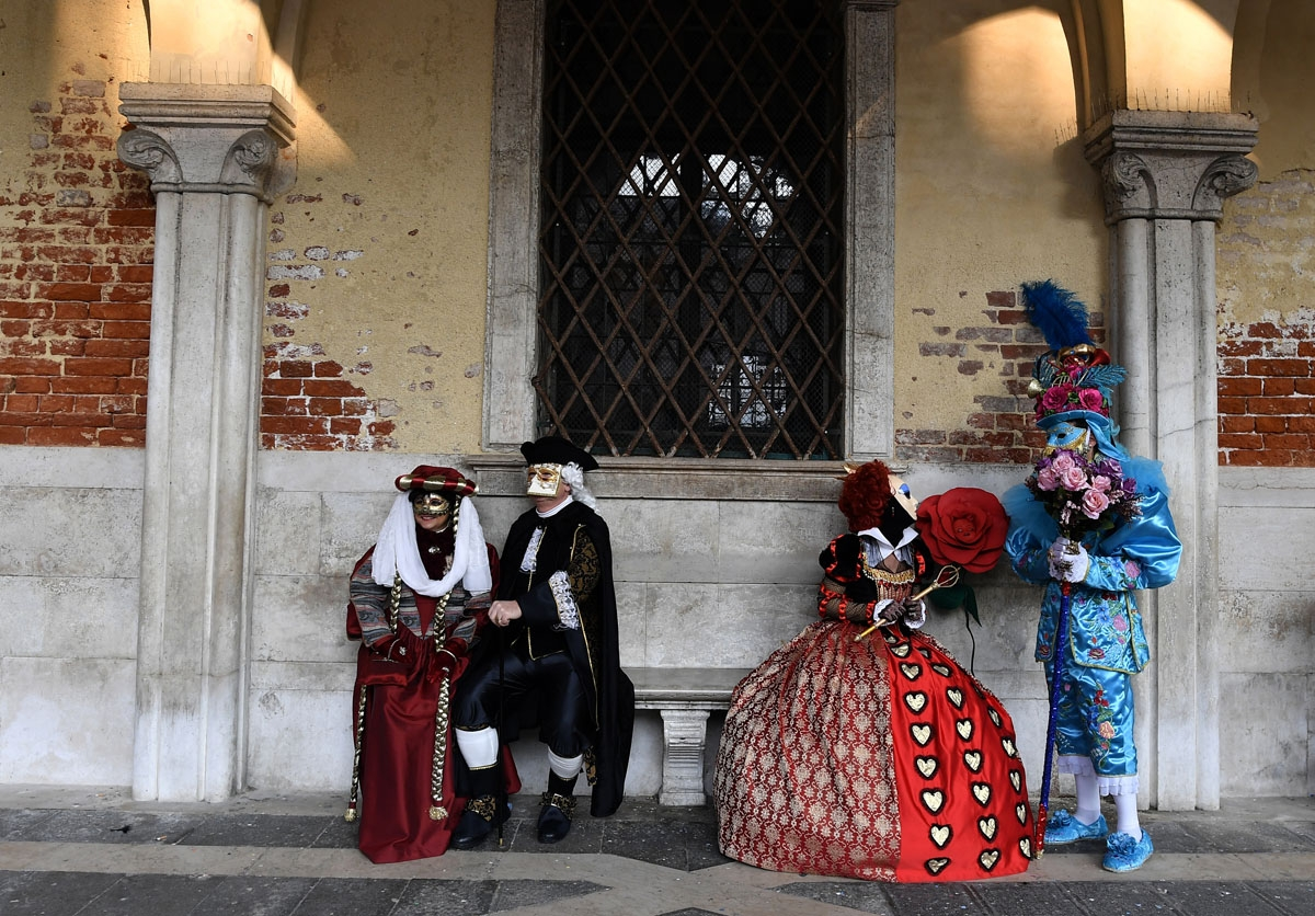 Masked revellers wearing traditional carnival costumes pose in Saint Mark Square during Venice's Carnival on February 4, 2018.