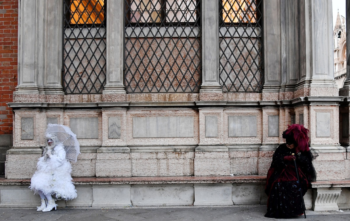 Masked people wearing traditional carnival costumes sit on a bench in Saint Mark Square in Venice, during Venice's Carnival on February 4, 2018.