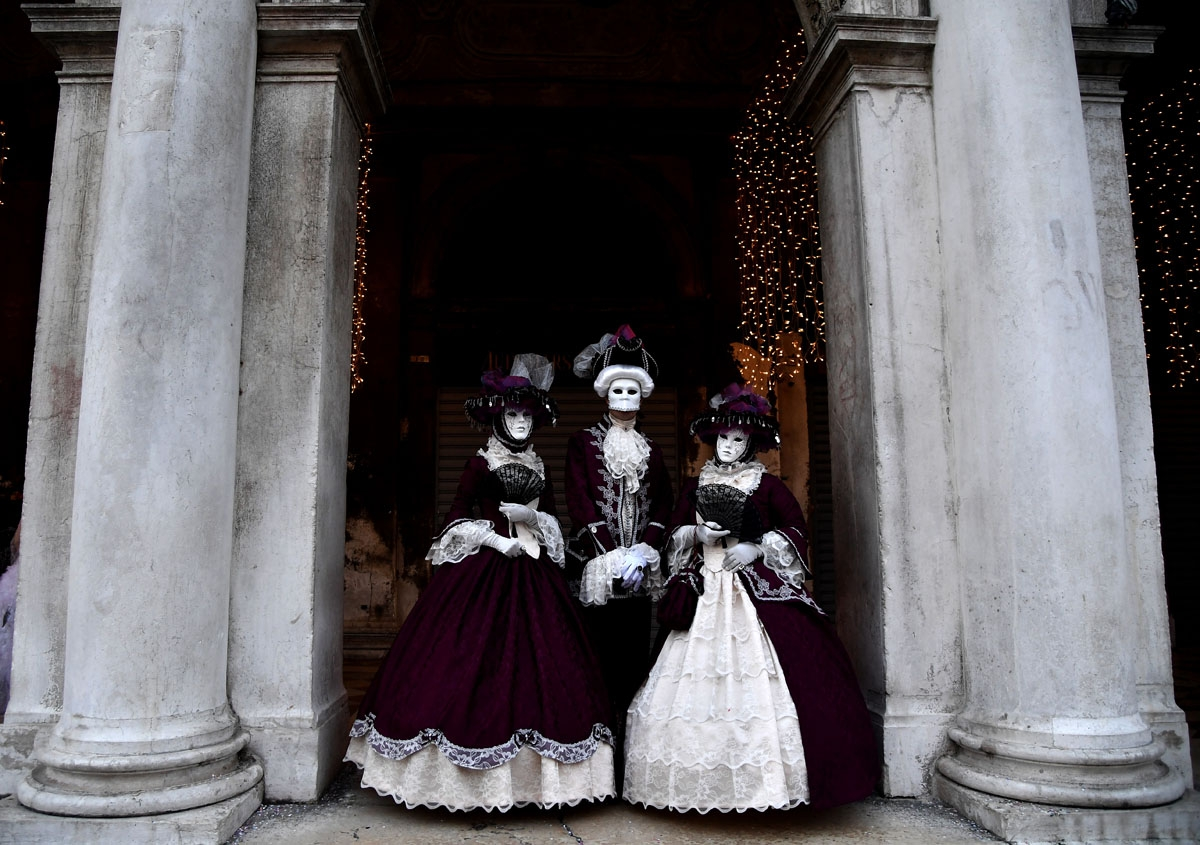 A masked people wearing traditional carnival costumes pose in Saint Mark Square in Venice, during Venice's Carnival, on February 4, 2018. / A
