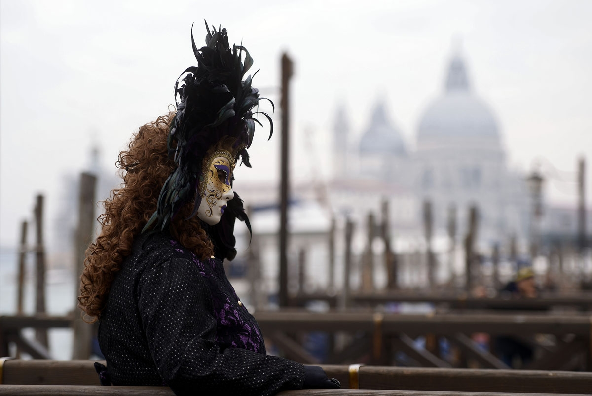 A masked reveller dressed in a period costume takes part in the Venice Carnival on January 27, 2018.