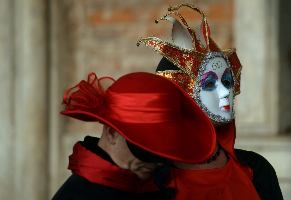 Masked revellers wearing traditional carnival costumes stand in St Mark Square during Venice's Carnival on January 28, 2018. /