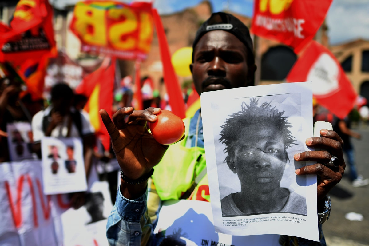 A demonstrator holds up a photo of Soumaila Sacko during a march organized by Italy's USB (Base Union of Trade Unions) against the murder of the USB syndicalist Sacko and the refusal by Italy to except migrants rescued at sea earlier in the week to land i