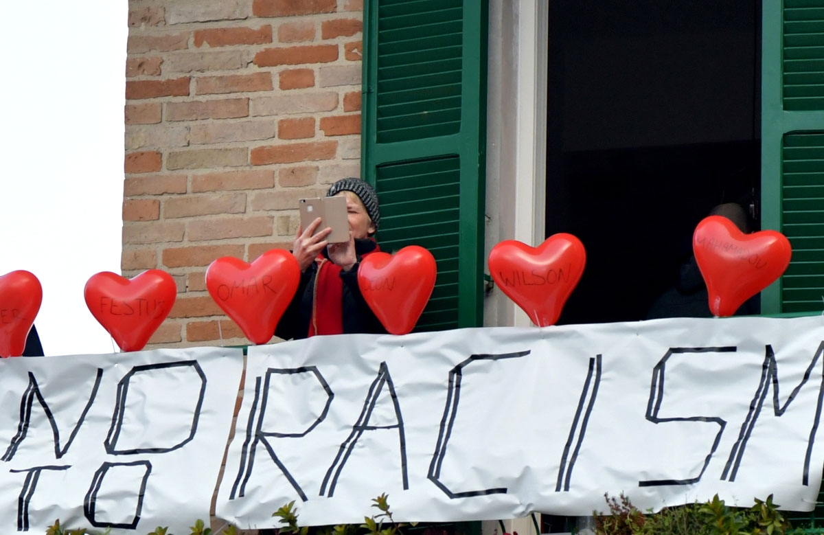 A woman stands on her balcony where she put red balloons with the victims' names and a banner reading no to racism during an anti-racism demonstration in the central Italian town of Macerata, on February 10, 2018, one week after an attack that injured at