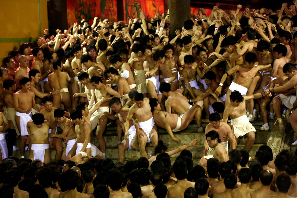 In this picture taken on February 18, 2017, worshippers fall down the stairs while waiting for the priest to throw the sacred batons during the annual Naked Man Festival or 'Hadaka Matsuri' at Saidaiji Temple in Okayama, western Japan.