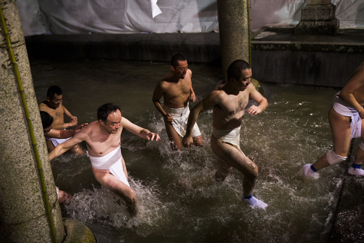In this picture taken on February 18, 2017, worshippers step out of a fountain after being purified during the annual Naked Man Festival or 'Hadaka Matsuri' at Saidaiji Temple in Okayama, western Japan.