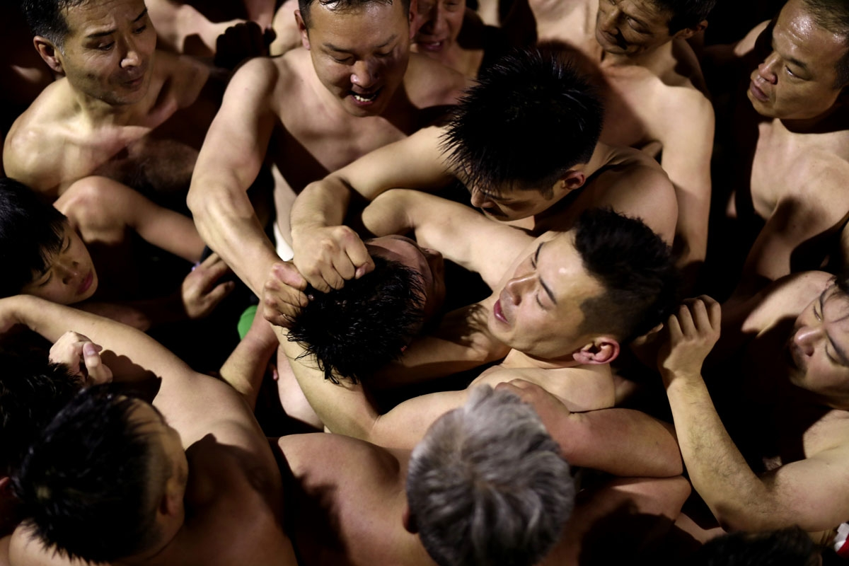 In this picture taken on February 18, 2017, worshippers fight to catch the thrown sacred batons during the annual Naked Man Festival or 'Hadaka Matsuri' at Saidaiji Temple in Okayama, western Japan.