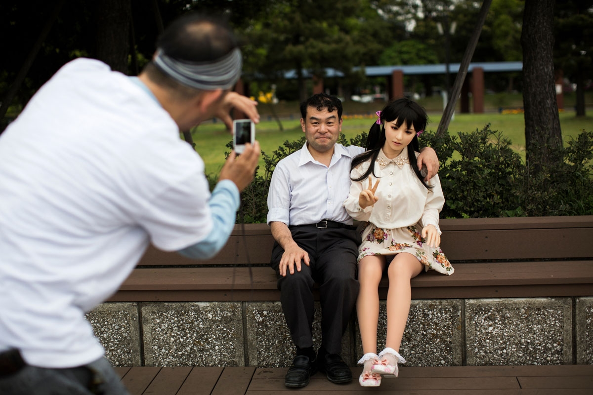 In this picture taken on May 9, 2017, a man takes pictures of physiotherapist Masayuki Ozaki and his silicone sex doll Mayu in Tokyo Bay.