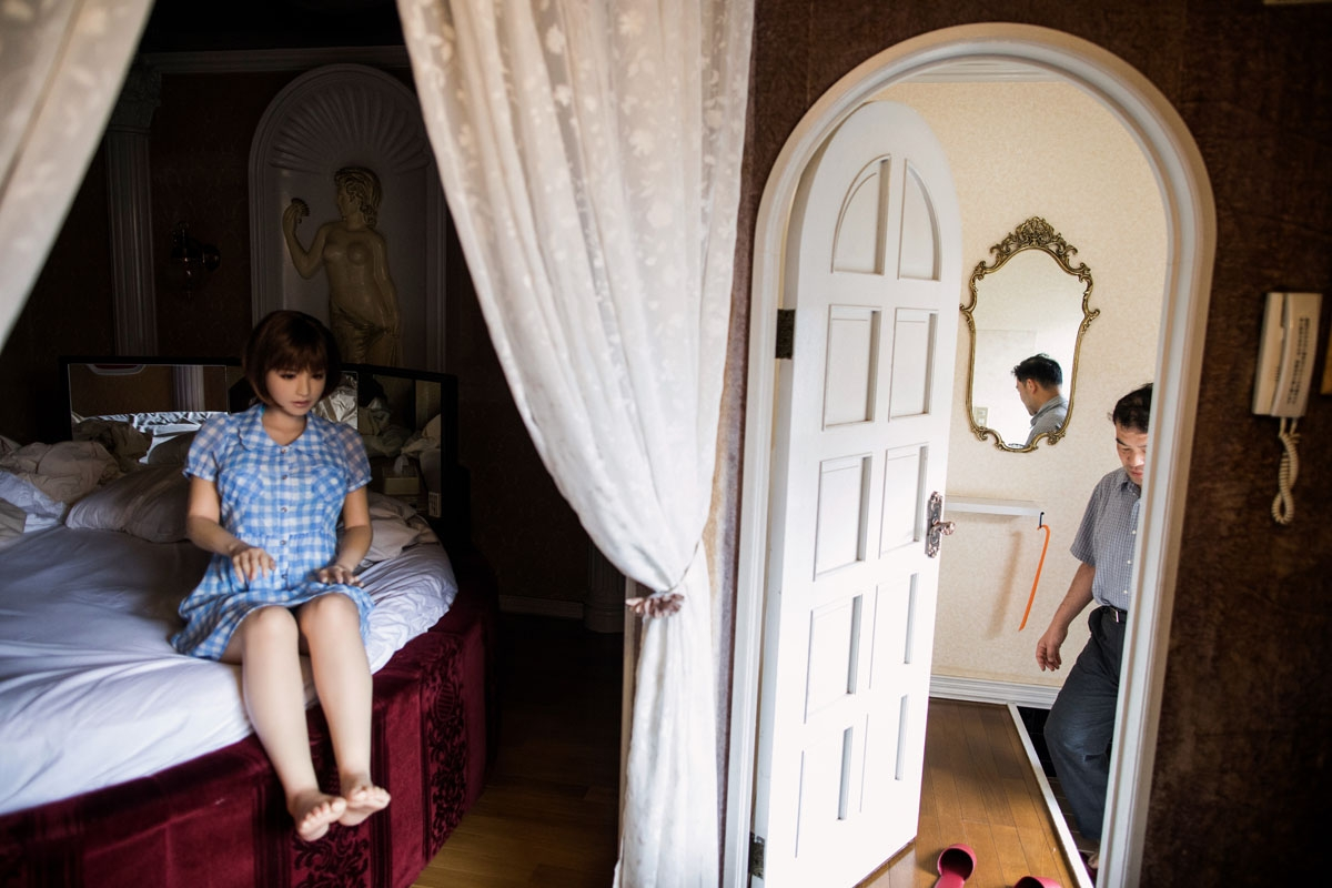 In this picture taken on June 14, 2017, physiotherapist Masayuki Ozaki (R) prepares to check out of a love hotel after spending a night with his silicone sex doll Mayu in Yachimata, Chiba prefecture.