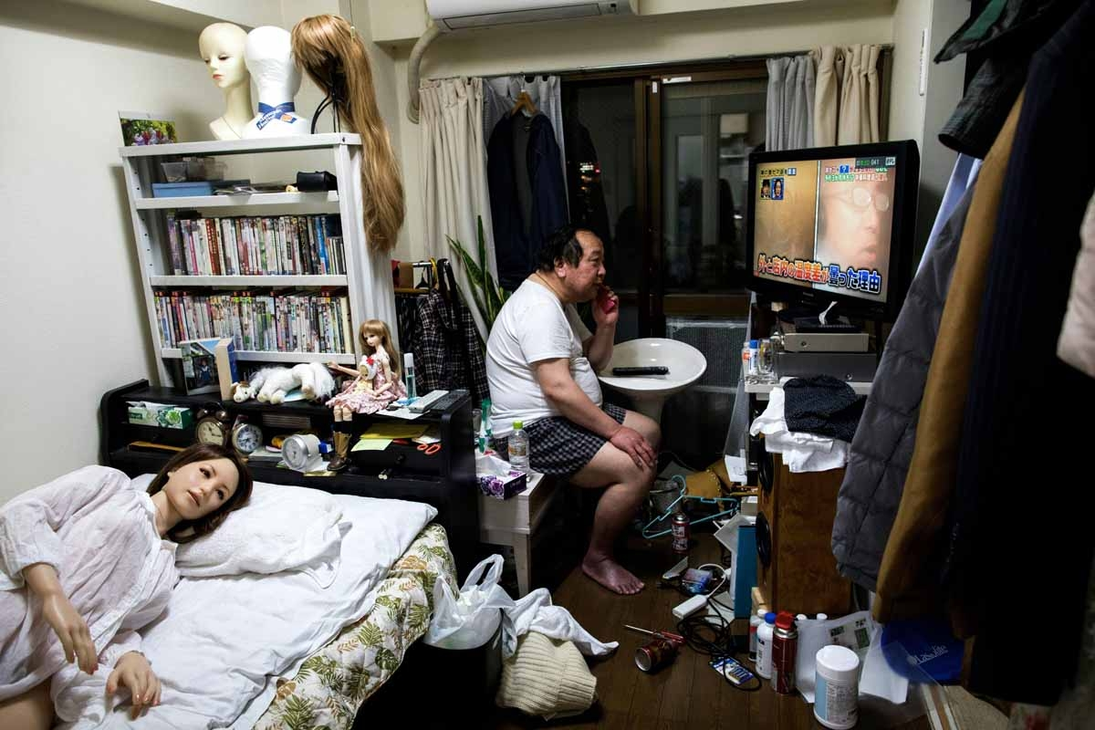 In this picture taken on April 20, 2017, 62-year-old Senji Nakajima speaks on his mobile phone as his silicone sex doll Saori (L) lies in bed at his apartment on the outskirts of Tokyo.