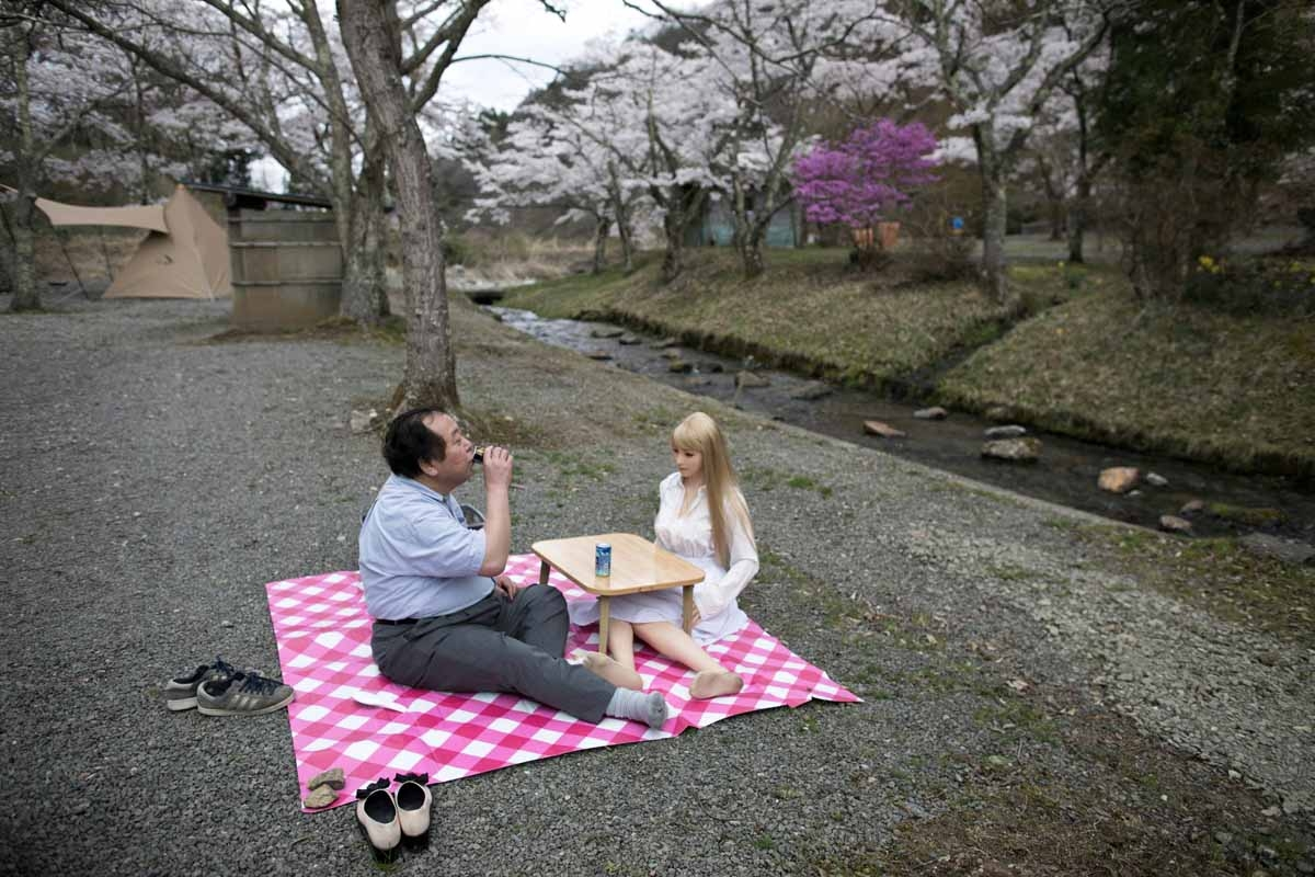 In this picture taken on April 21, 2017, 62-year-old Senji Nakajima (L) picnics with his silicone sex doll Saori under cherry blossoms in Yamanashi prefecture.