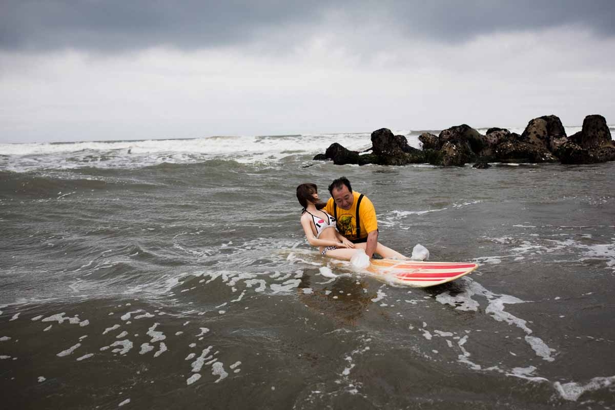 In this picture taken on June 14, 2017, 62-year-old Senji Nakajima tries to surf with his silicone sex doll Saori at Kujukuri beach, Chiba prefecture.