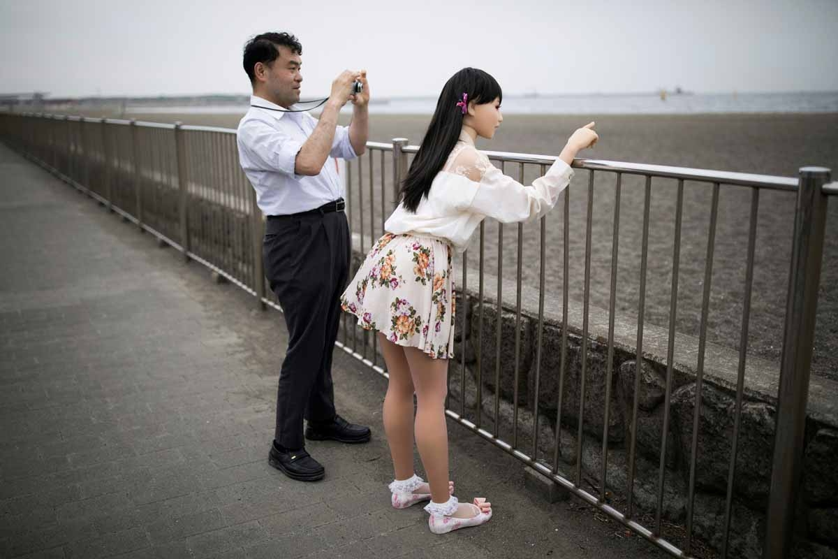 In this picture taken on May 9, 2017, physiotherapist Masayuki Ozaki (L) takes pictures of his silicone sex doll Mayu in Tokyo Bay.