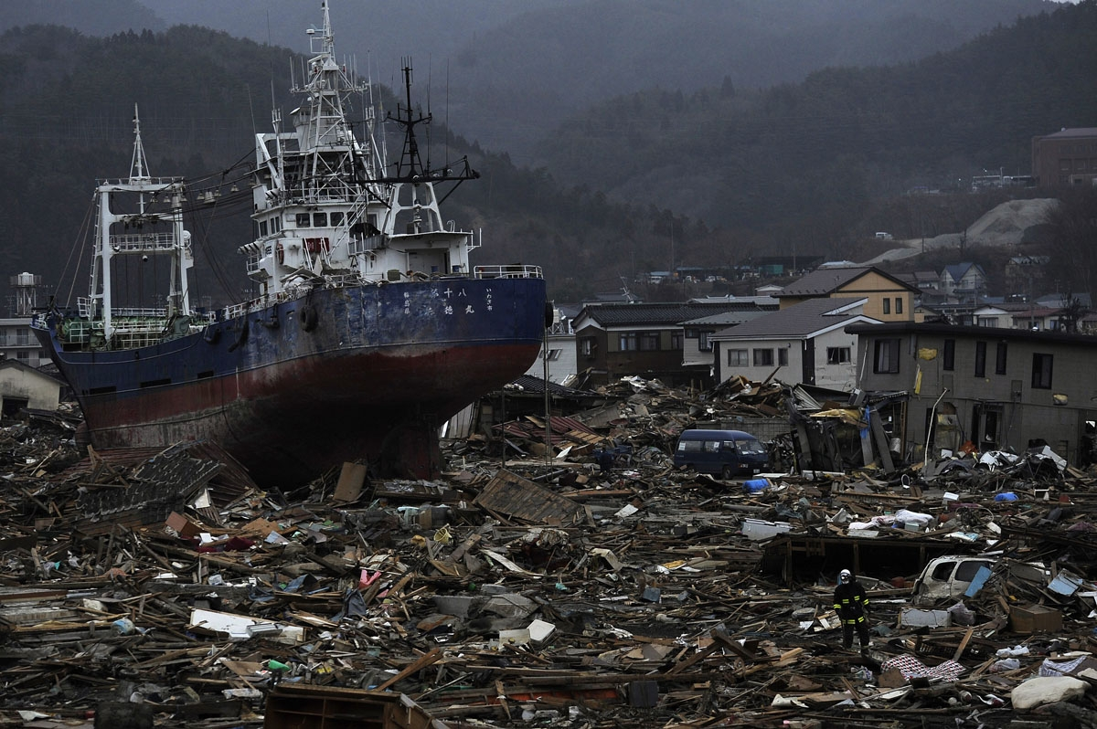 A Japanese firefighter (R) walks past a boat pushed inland by the March 11 tsunami in Kesennuma in Miyagi prefecture on March 20, 2011.